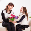 Girl giving her mother flowers — Stock Photo #50507667