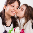 Girl kissing and giving mother flowers — Stock Photo