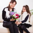 Girl giving her mother flowers — Stock Photo