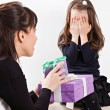 Mother giving daughter surprise gift — Stock Photo #50509435