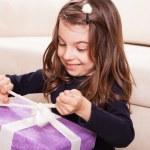Girl holding purple present box — Stock Photo #50509473