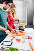 Couple cooking together in kitchen — Stock Photo