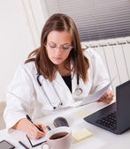 Female doctor working in office — Stock Photo