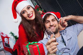 Couple holding Christmas presents and champagne — Stock Photo