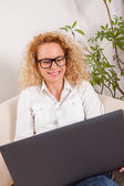 Girl working on laptop at home — Stock Photo