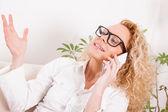 Girl having phone conversation at home — Zdjęcie stockowe