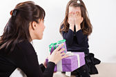 Mother giving daughter surprise gift — Stock Photo