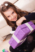 Girl holding purple present box — Stock Photo