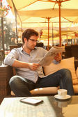Man reading newspapers and drinking coffee — Stock Photo