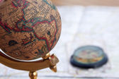 Ancient globe and compass over a map — Stock Photo