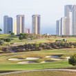 Stock Photo: Golf field with skyscrapers in city of Benidorm, Spain