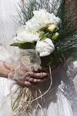 Two hands holding a bridal bouquet at a wedding — Stock Photo