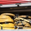 Rolled and yellow fire hoses on a fire truck — Stock Photo