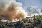 Fire burning mountain forest and village, danger for the houses — Photo