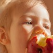 Child girl eating big red apple — Stock Photo #42261115