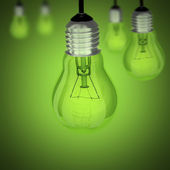Turned off light bulb on green background — Stock Photo