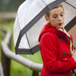 Lonely girl in a park in a rainy day with umbrella — Stock Photo