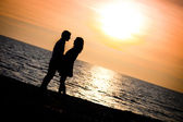 Lovers Kissing on the beach at sunset — Stock Photo