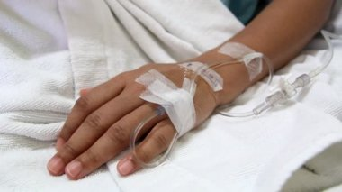 Closeup saline goutte à goutte dans le patient la main sur le lit à l'hôpital — Vidéo