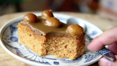 Spoon cutting coffee cake with macadamias on top — Stock Video