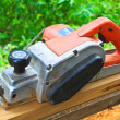 Close up construction worker's hand and power tool while planing — Foto de Stock