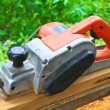 Close up construction worker's hand and power tool while planing — Stok fotoğraf