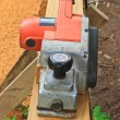 Close up construction worker's hand and power tool while planing — Stockfoto
