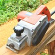 Close up construction worker's hand and power tool while planing — Stockfoto #34563527