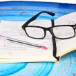 Glasses, notebook and pen on the homework  — Stock Photo