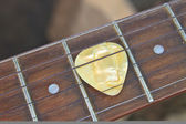 Guitar pick on the fingerboard — Stock fotografie