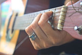 Girl hand playing acoustic guitar — Stock Photo