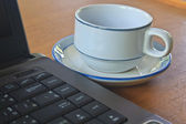 Coffee cup and laptop  on table — Stock Photo