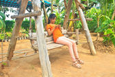 Young girl sitting on the wooden swing with mobile phone — Stock fotografie