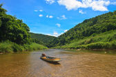 River in evergreen forest with boat — Stock Photo