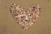 Heart made of sea shells lying on a beach sand — Stock Photo
