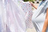 Pregnant woman dry the cloth diaper in the sun — Stock Photo