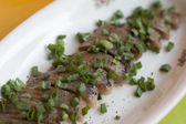 Herring fillet with green onion on a plate — Stock Photo