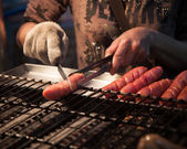 Man cutting Chinese sausage at Night market — Stock Photo