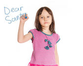 Young girl writing to Santa on imaginary board — Stock Photo