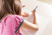 Child writing her homwork at a desk with a blue pencil crayon — Stock fotografie