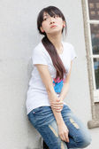 Asian girl against wall — Stock Photo