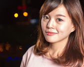 バック グラウンドで街の灯を持つかなりアジア女性 — ストック写真