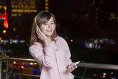 Linda mulher asiática usando fones de ouvido e segurando o telefone celular — Fotografia Stock