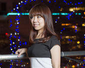 Smiling Asian woman in front of city lights — Stock Photo