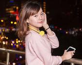 Hermosa mujer asiática con teléfonos inteligentes y los auriculares amarillos — Foto de Stock