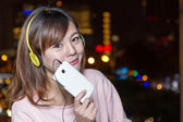 Beautiful young Asian woman wearing yellow headphones — Stock Photo