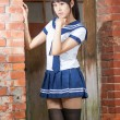 Asian schoolgirl in uniform outside school — Stockfoto