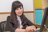 Chinese businesswoman at desk smiling — Stockfoto