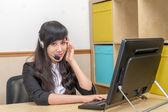 亚洲名年轻女子在呼叫中心有点恼了 — 图库照片