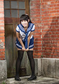 Asian schoolgirl in uniform outside school — Stock Photo